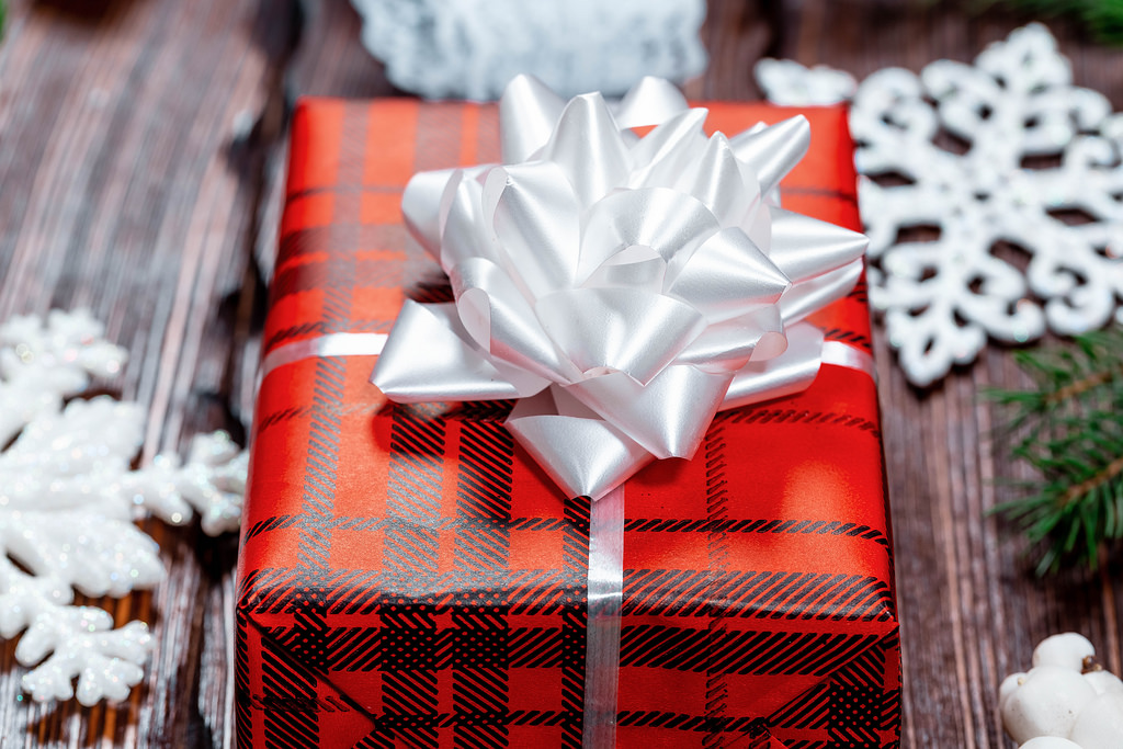 a gift in wrapping paper surrounded by paper snowflakes
