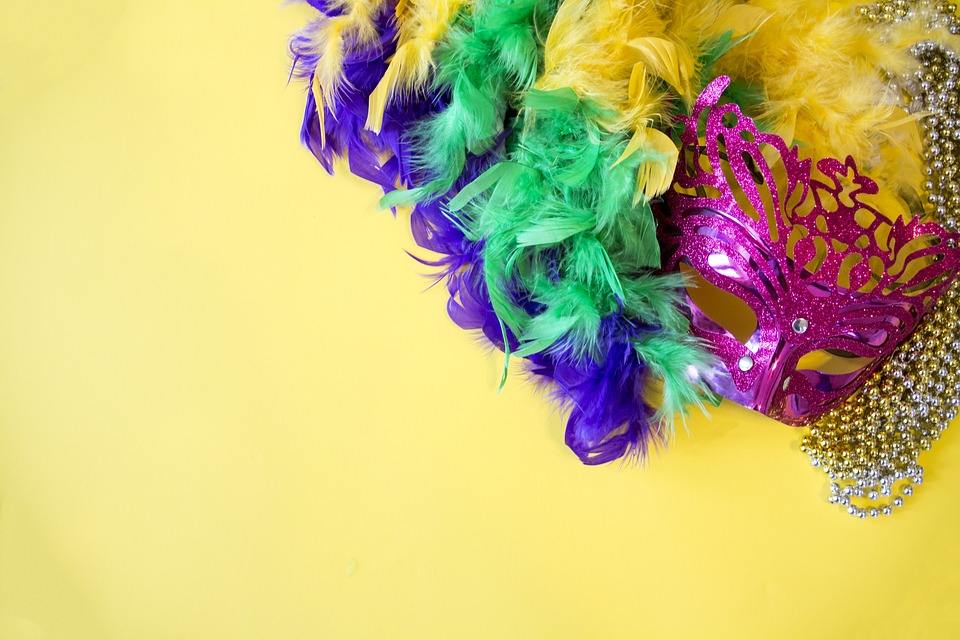 pink mardi gras mask on yellow background