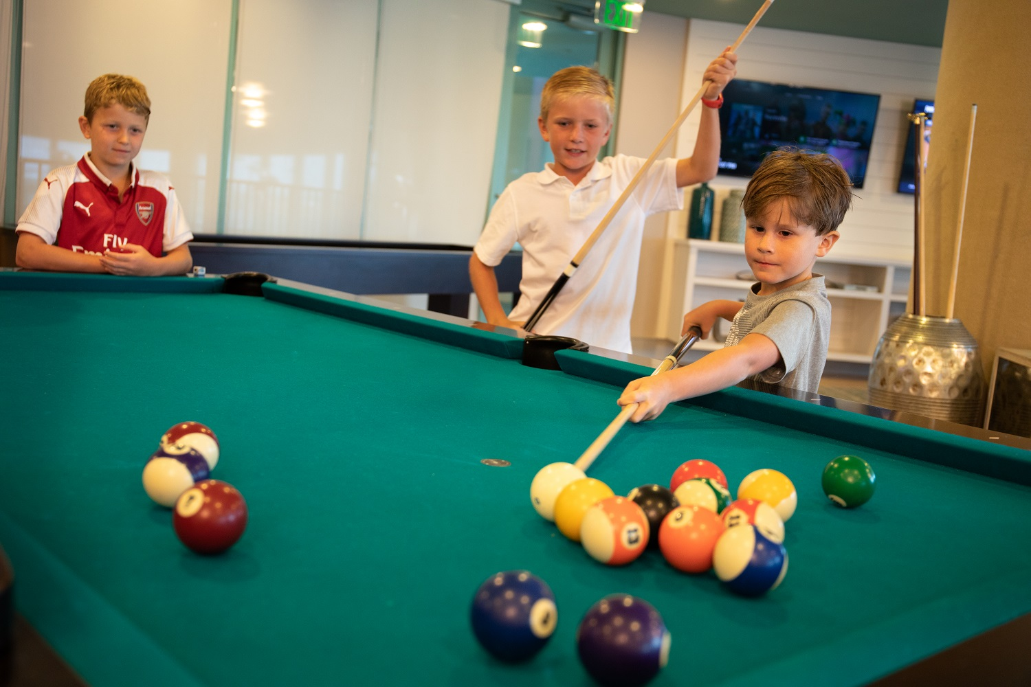 kids playing billiards at the spectrum club lounge
